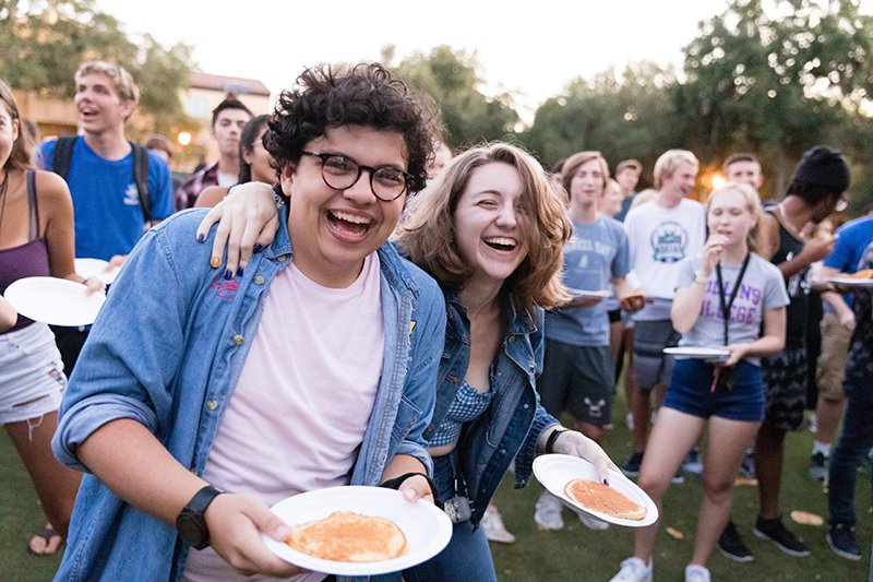 Students laugh while they try to catch pancakes on their plates during orientation.