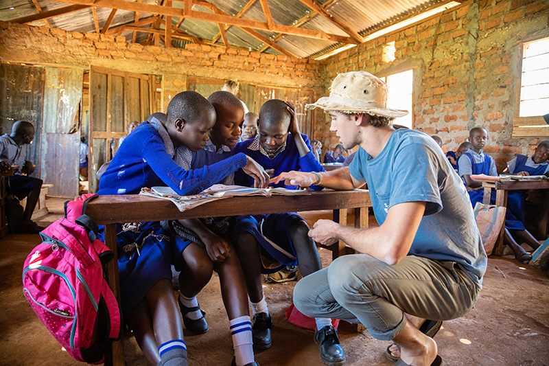 A Rollins student helps children in Tanzania study.