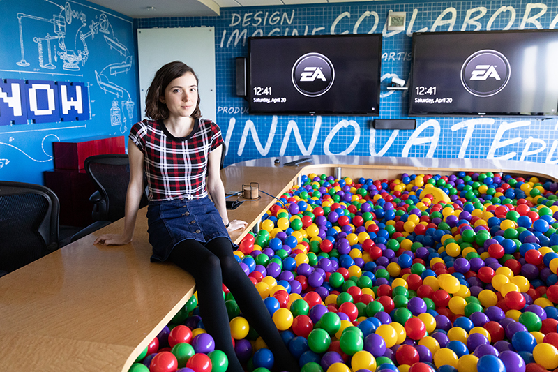 Woman sits on the edge of a ball pit in the middle of a conference room at EA Sports' Orlando headquarters.