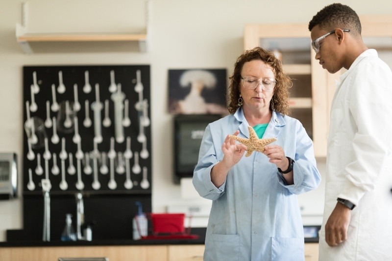 Professor in a pale blue lab coat, stands with a student, while holding a starfish and they both examine.