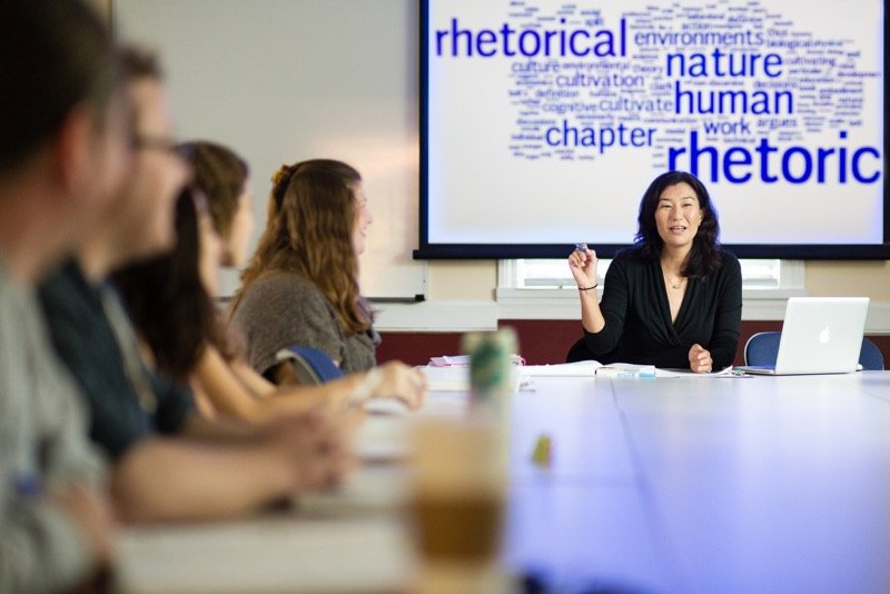 Professor at the head of a table, with five students sitting to her right. Behind the professor, on a projection screen is a word cluster with words like rhetoric, rhetorical, and chapter large.