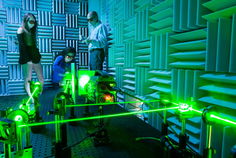 Professor and two students in a sound proof lab, wearing protective eye gear, turn a green laser on which reflects through an object they are testing.