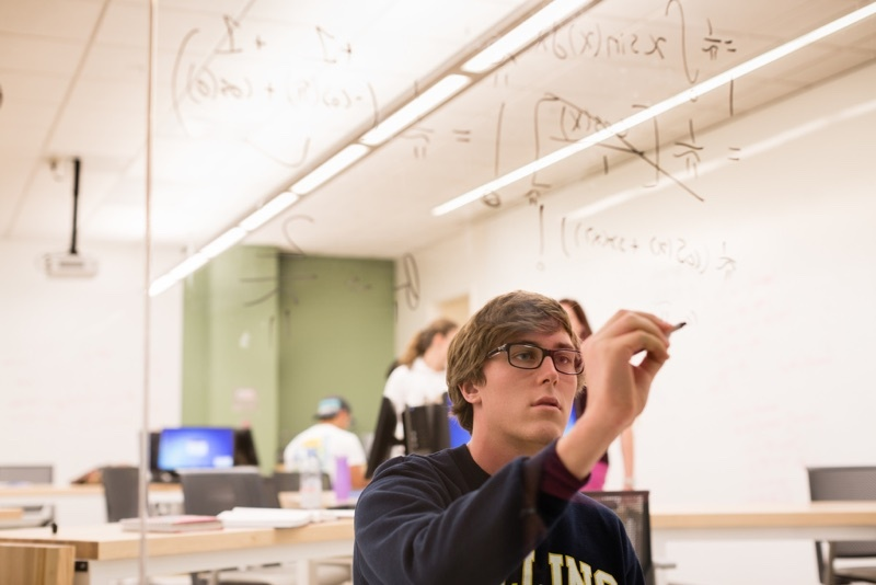Looking at a student writing on a glass wall in a Rollins science lab.