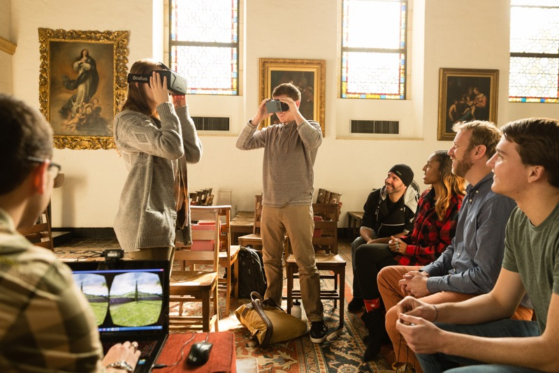 Two students stand in the middle of a classroom with Virtual Reality headsets on, while the professor and four students watch them.