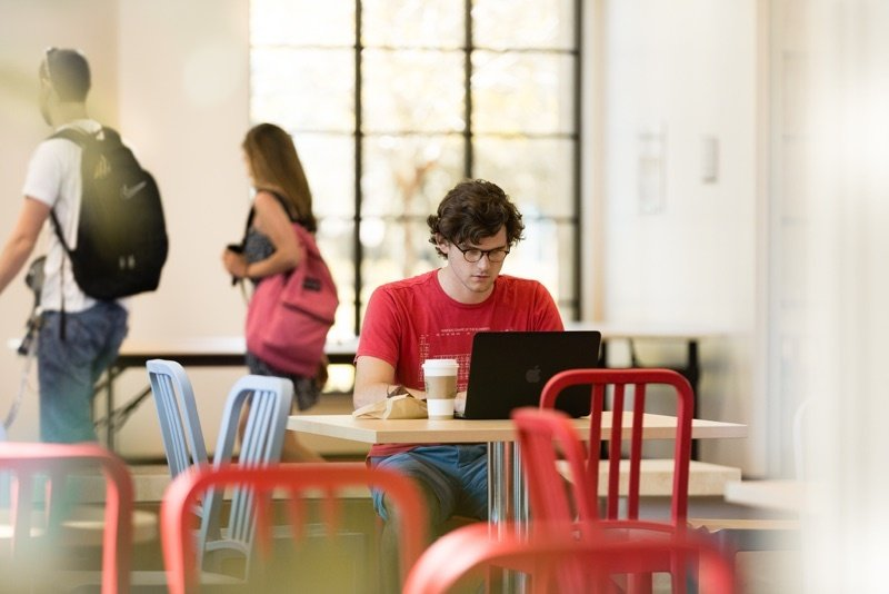 Male student at a table at a Rollins cafe, in front of his laptop as students walk by him on their way to class.
