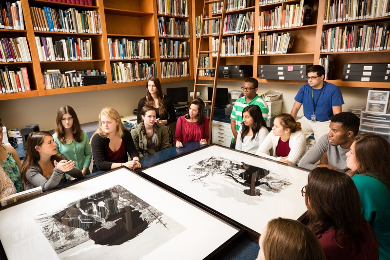 A dozen students surround a large table with two pieces of art on it, as they have a group discussion.