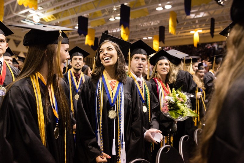 Female college graduate celebrates during a commencement ceremony.
