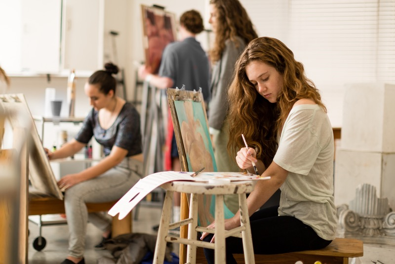 Art class. Students sit and stand in front of easels painting their latest masterpiece.