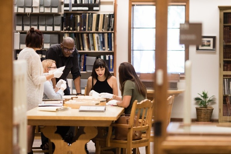 Professor and students sit and stand around a table in the Rollins Archives, pouring over books and documents.