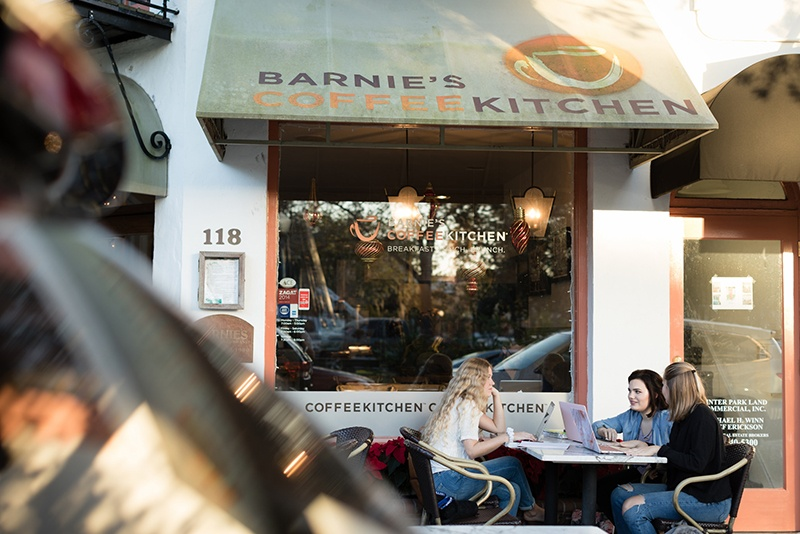 Students work on a project at a table outside a coffee shop in Winter Park, Florida.