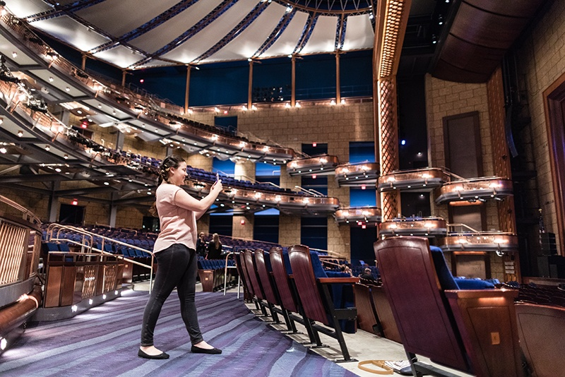 A social media intern takes photos on her phone at a performing arts center.