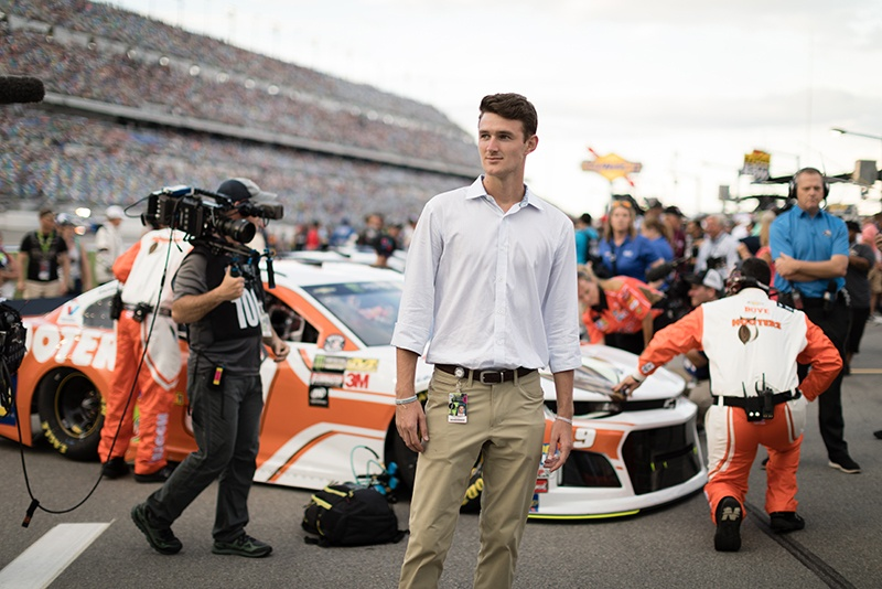 Intern stands in front of a NASCAR race car at Daytona International Speedway.