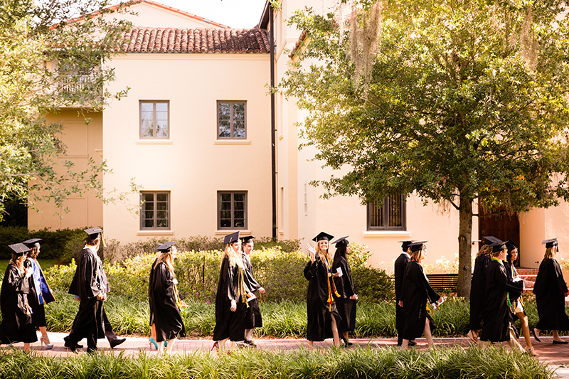 Students walking on campus during a commencement ceremony.