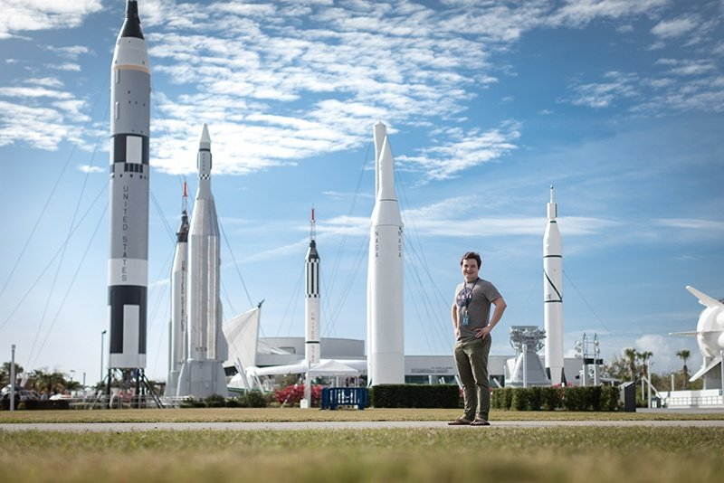 Student is surrounded by rockets as he walks around NASA's Kennedy Space Center.