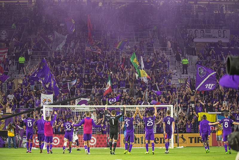 Soccer players celebrate with fans at Orlando City Soccer Stadium in Orlando.
