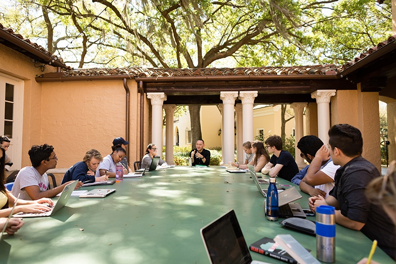 College professor and students engage in discussion in a outdoor classroom.