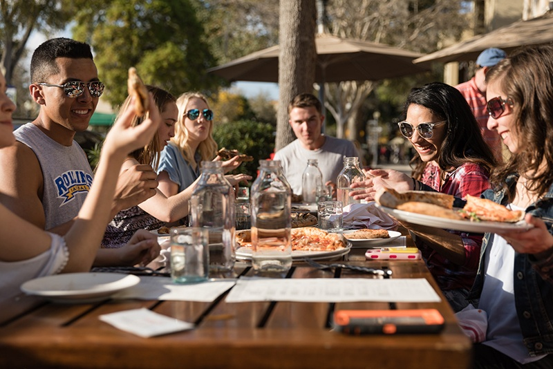 Florida college students eat pizza outdoors at Prato restaurant in Winter Park.