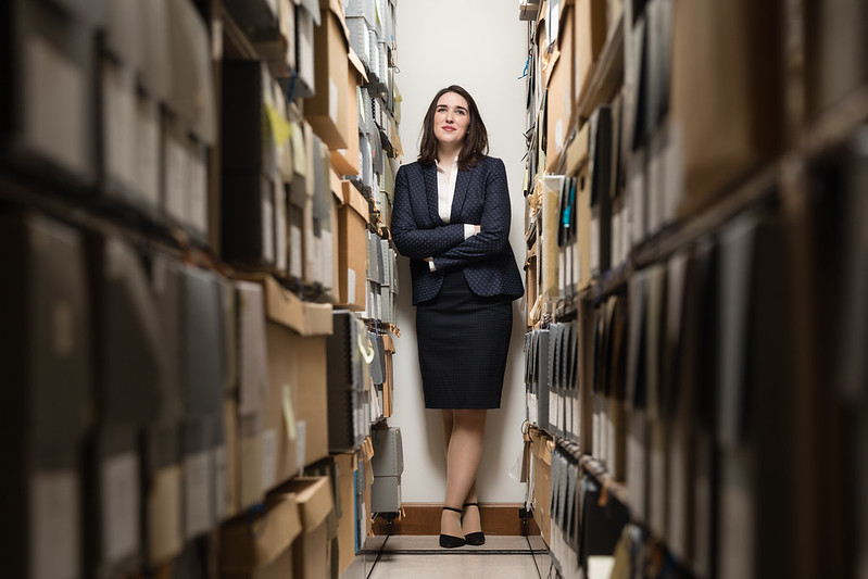 Female student poses between the stacks in a library's archives.