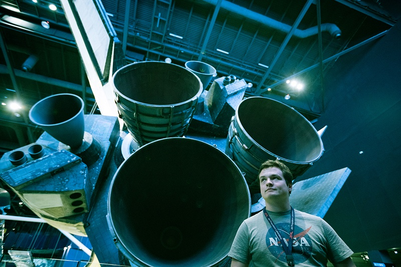 Male student stands in front of a space shuttle at NASA's Kennedy Space Center.