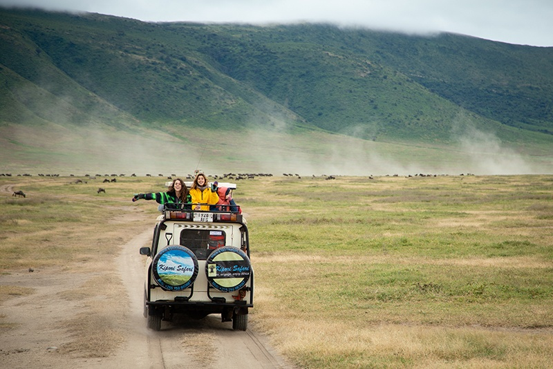 Students on a safari jeep in the middle of Serengeti National Park in Tanzania.