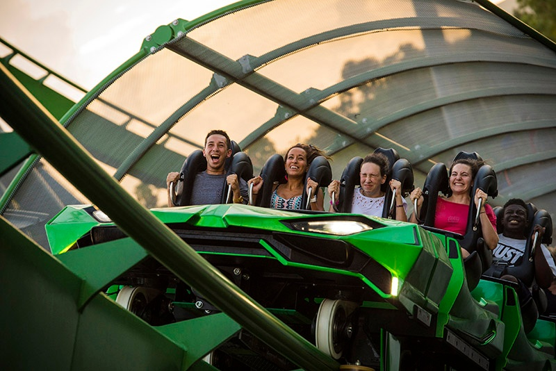 College students yell in excitement while riding a roller coaster at Universal Studios.